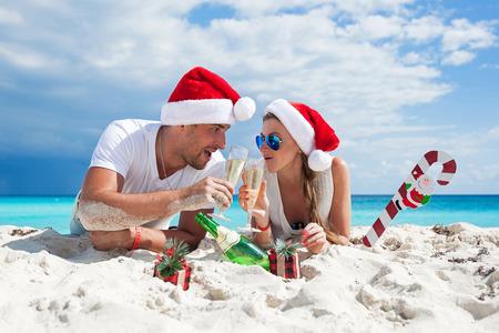 enjoying life: Happy couple celebrating Christmas on beach in Santa hats. Champagne toast outdoors, people enjoying life