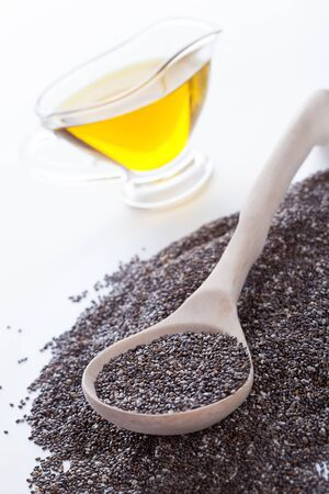 omega3: Dry chia seeds in spoon on Omega3 plant oil background