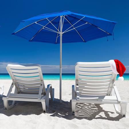 sun umbrellas: Caribbean beach with blue sun umbrellas and white sunbeds. Christmas vacation. Santa hat on sun chair Stock Photo