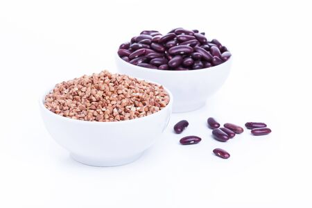 caloric: Dry buckwheat and black beans in white bowl, source of Iron (Fe) Stock Photo