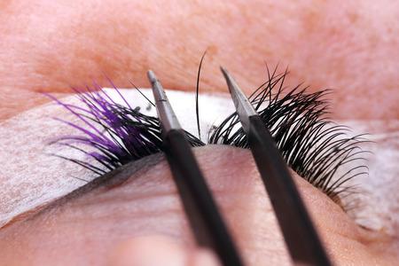 Lash making process, extreme long lashes and tweezers, woman eyelash extension Stock Photo