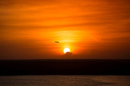 sun down: Beautiful yellow sunset with airplane in the sky. Tropical sun down. Aerial view Stock Photo