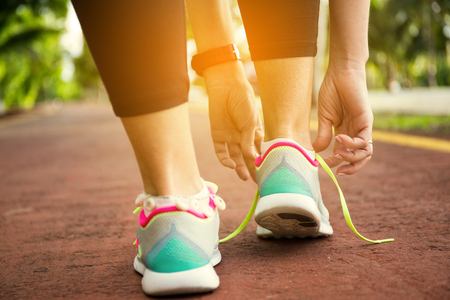 Fitness woman tying running shoe laces, ready for jogging in summer park. Healthy lifestyle and sport concept Standard-Bild