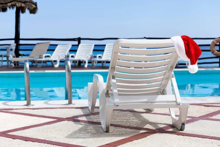 bahamas celebration: Santa Helper Hat on Lounge sunbed near swimming pool, outdoor near caribbean sea