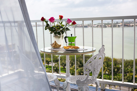 Delicious breakfast with coffee on hotel's balcony, decorated with fresh roses, croissants and slice of orange fruit with coffee percolator background, overlooking sea view