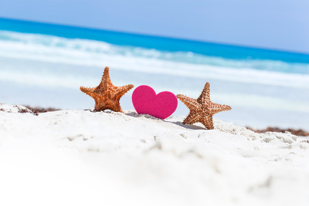 sweet heart: Red sweet heart shape with two starfishes on white sandy beach with sea background. Happy Valentines Day at summertime on exotic vacations.