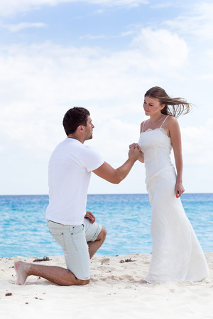 Man down on one knee and asking for marry his woman, holding her hand on sandy beach near sea at Caribbean vacation. Free copyspace on sky background. Stock Photo - 60031364