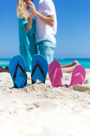 Pair of color flip flops on sandy beach near sea with romantic couple on background. Focus on slippers. Happy travel concept Stock Photo