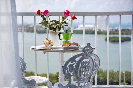 Delicious breakfast with coffee on hotels balcony, decorated  with fresh roses, croissants and slice of orange fruit with coffee percolator background, overlooking sea view Stock Photo