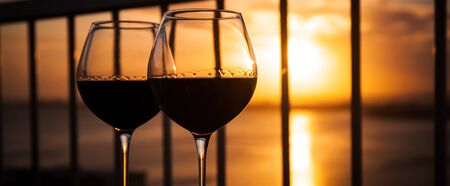 balcony view: Two red wine glasses in front of the setting sun. Balcony view with Caribbean sea background