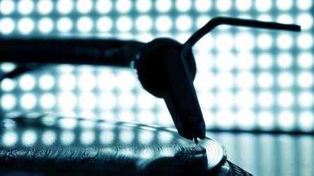 Dj needle stylus on spinning record, blur light background Stock Photo
