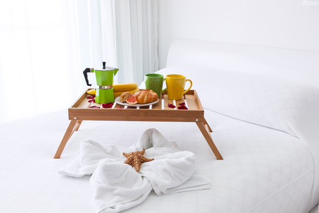 Breakfast wooden tray with coffee percolator and croissant on bed, decorated starfish on white towel