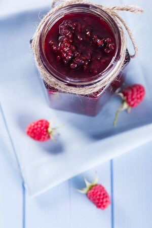 organic raspberry: Homemade organic raspberry jam in jar with fresh berries on wooden table, selective focus, top view