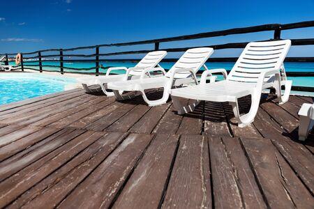 sunbeds: Luxury sunbeds on wooden floor near swimming pool, outdoor near caribbean sea