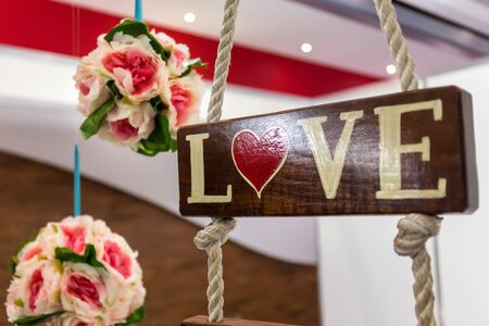 hanged woman: Wedding decoration. Bouquet of flowers and wooden board with sign Love and shape of heart on it Stock Photo
