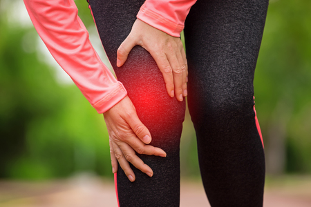 Female athlete runner touching Knee in pain, fitness woman running in summer park. Healthy lifestyle and sport concept
