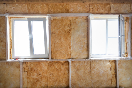 rockwool: Inside wall heat isolation with mineral wool in wooden house,  building under construction Stock Photo