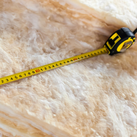 glasswool: Measure tape on mineral wool, closeup