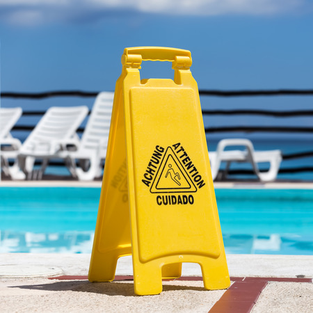 Wet floor warning sign near a swimming pool
