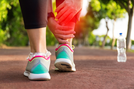 sprained joint: Female athlete runner touching foot in pain,closeup, fitness woman running in summer park. Healthy lifestyle and sport concept
