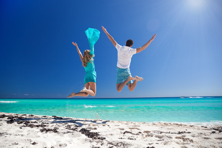 Happy couple jumping with outstretched arms on beach and enjoying their caribbean vacation. Back view Stock Photo