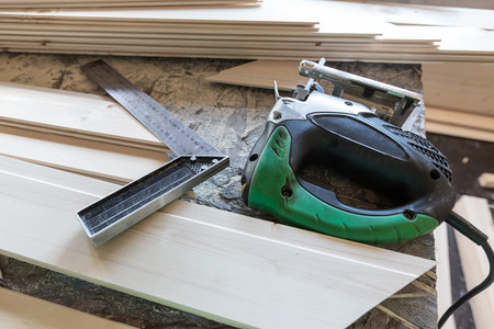groove: Fretsaw, metal ruller and tongue and groove boards on working place, closeup Stock Photo