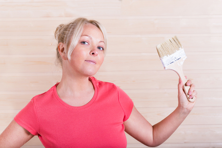 Woman with paint brush in hand on wooden slot and key boards background Stock Photo