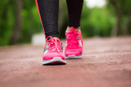 Fitness woman training and jogging in summer park, close up on running shoes. Healthy lifestyle and sport concept