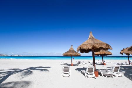 palapa: Beach chairs and grass umbrellas on a stunning tourist resort beach