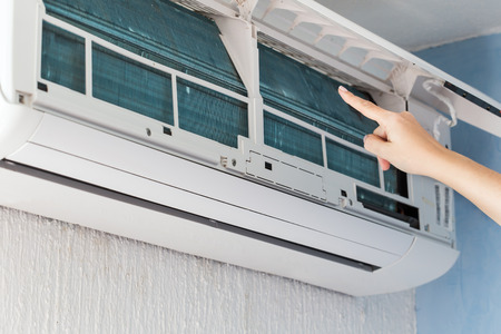 Finger show on dirty filter of air conditioner. It's time to Cleaning and washing maintenance