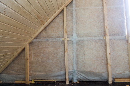 groove: Heat insulation and wooden logs lathing ready for Finishing made of tongue and groove planks. An interior view of unfinished home inside Stock Photo