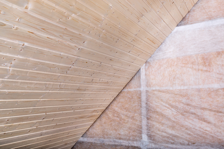 glasswool: Heat insulation and wooden logs lathing ready for Finishing made of tongue and groove planks. An interior view of unfinished home inside Stock Photo