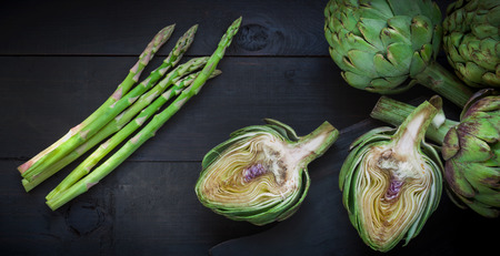 Fresh green artichokes  and asparagus on wooden cutting board, selective focus