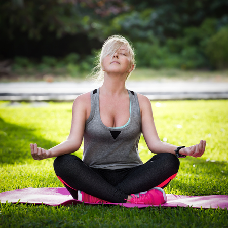 sit down: Woman meditating on green grass at the park sitting in lotus position. Fitness girl relaxing in yoga pose after exercises Foto de archivo