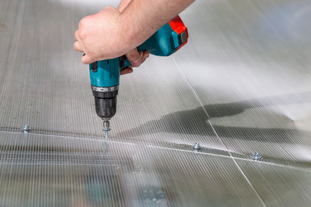Worker screwing screw into polycarbonate. Building greenhouse