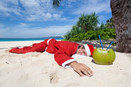 Santa Claus lying on sand in tropic paradise photo