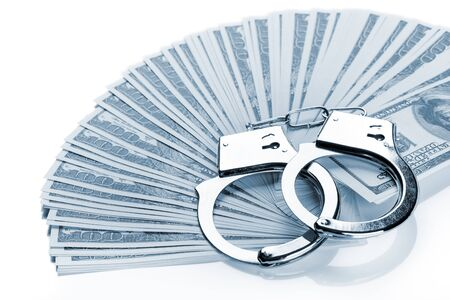 Pair of handcuffs closeup on dollar banknotes fan. Corruption problem in the world