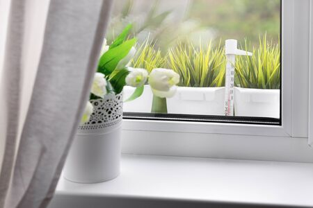 Bouquet of tulips in white vase on windowsill