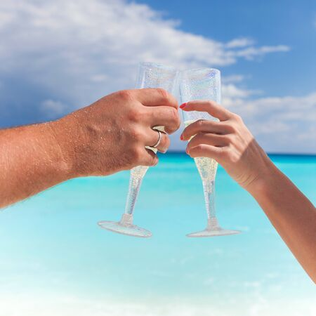 Toast champagne on beach with caribbean sea background. Two flute champagne glasses in hands, close up. Celebrating holidays