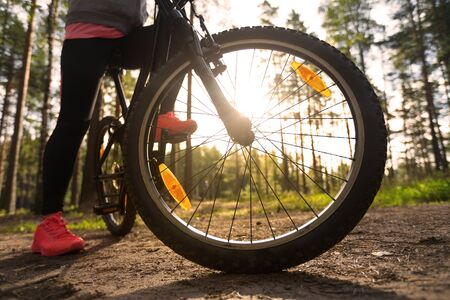 spokes: Woman riding a mountain bicycle along path at the forest. Closeup on wheel with spokes. Healthy lifestyle and sport concept Stock Photo