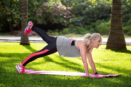 Jonge mooie fitness vrouw met paardenstaart doet plank positie buiten op het groene gras in het park