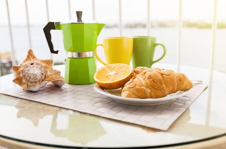 Delicious breakfast with coffee on hotels balcony, fresh croissants and slice of orange fruit with coffee percolator background Stock Photo