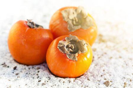 Three fresh orange persimmons on white snow, outside Stock Photo