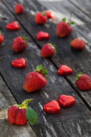 14: Fresh red strawberries and chocolate heart candy on old wooden table