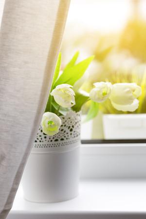windowsill: Bouquet of tulips in white vase on windowsill