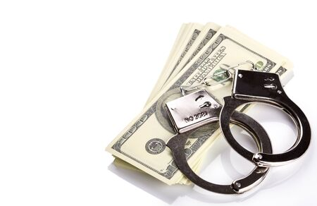 Pair of handcuffs closeup on dollar banknotes stack. Corruption problem in the world Stock Photo