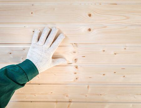 groove: Human palm in gloves on tongue and groove wooden planks wall, closeup
