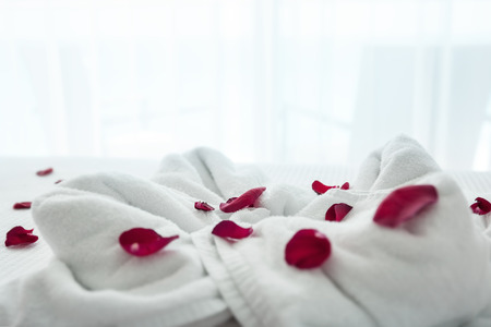 White towels decoration surround by red rose petals on bed with beautiful sea view