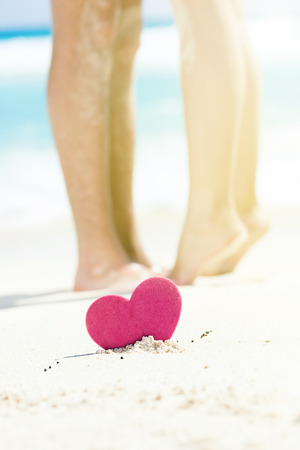 footsie: Barefoot female legs standing up tiptoe on mans foots on beach with turquoise sea background, decorated pink heart object.  Romantic St. Valentines card Stock Photo