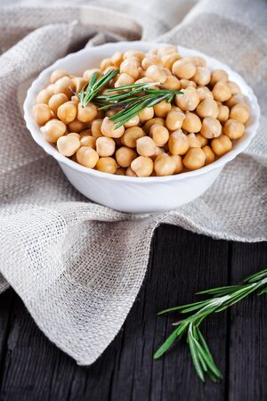 garbanzos: Gold chick peas in bowl with rosemary decorated tablecloth on wooden background, healthy vegetarian food with a lot of protein
